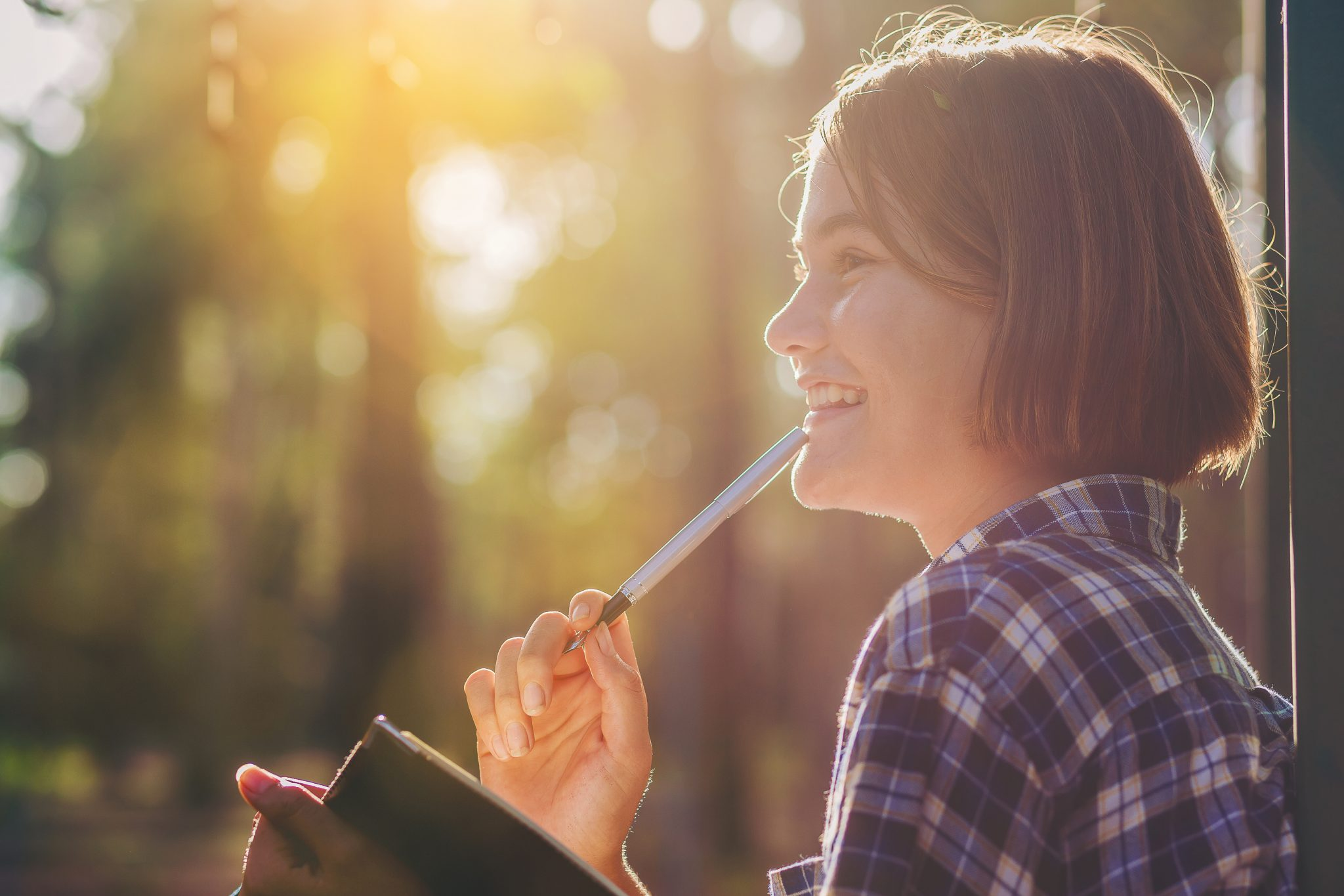 Pretty girl with notebook and pen make a shortnote while travel education along path of a big forest with sunrise.